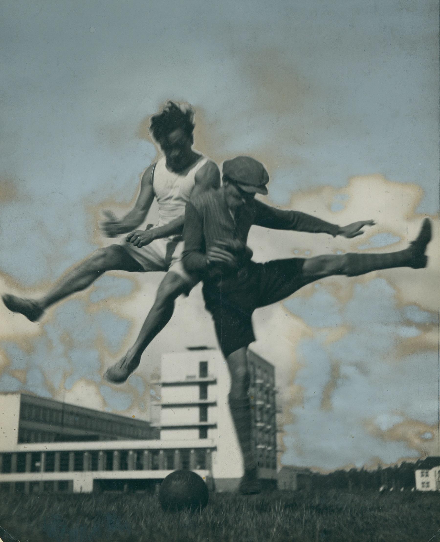 Dos miembros de la Bauhaus juegan al fútbol con la escuela al fondo. Xanti Schawinsky Estate/Nachlass Theodore Lux Feininger.