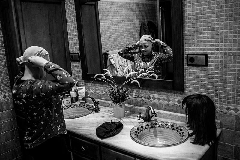 Raquel, sometida actualmente a un tratamiento de quimioterapia, mientras se pone la peluca en su casa, en un pueblo a unos 10 kilómetros de Murcia.